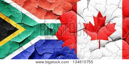 South africa flag with Canada flag on a grunge cracked wall