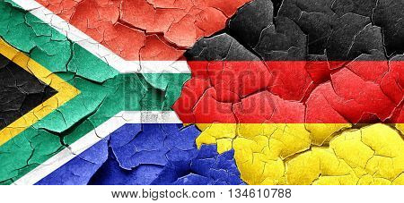 South africa flag with Germany flag on a grunge cracked wall