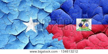 Somalia flag with Haiti flag on a grunge cracked wall