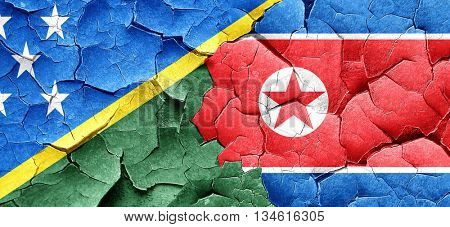 Solomon islands flag with North Korea flag on a grunge cracked w