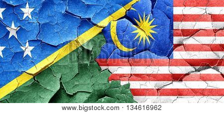 Solomon islands flag with Malaysia flag on a grunge cracked wall