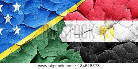 Solomon islands flag with egypt flag on a grunge cracked wall