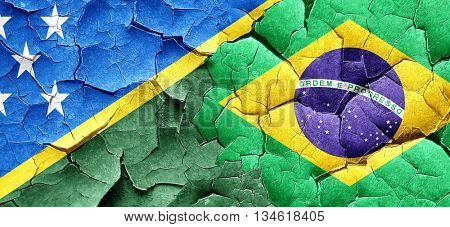 Solomon islands flag with Brazil flag on a grunge cracked wall