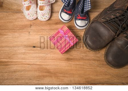 Daddy's Boots ,baby's Shoes ,textile Hearts ,gift On Wooden Background .fathers Day Concept