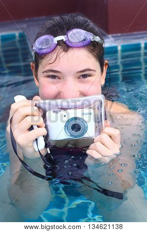 teenage pretty girl in water glasses close up portrait with camera in underwater protection slip in open air swimming pool