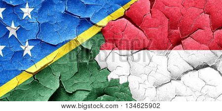 Solomon islands flag with Indonesia flag on a grunge cracked wal