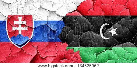 Slovakia flag with Libya flag on a grunge cracked wall