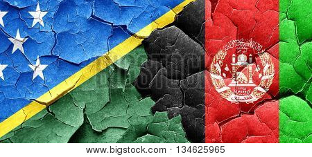 Solomon islands flag with afghanistan flag on a grunge cracked w
