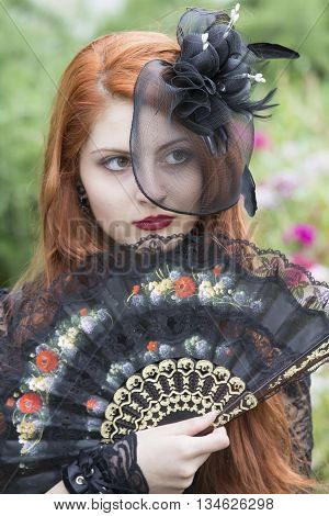 CAGLIARI, ITALY - June 1, 2014: Sunday at La Grande Jatte public gardens - Sardinia - portrait of a beautiful girl with a fan in Victorian costumes