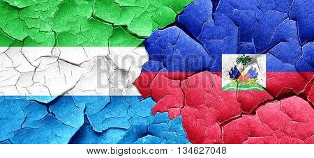 Sierra Leone flag with Haiti flag on a grunge cracked wall