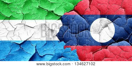 Sierra Leone flag with Laos flag on a grunge cracked wall
