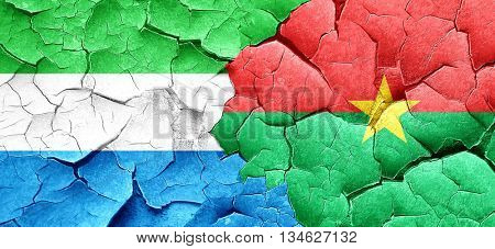 Sierra Leone flag with Burkina Faso flag on a grunge cracked wal