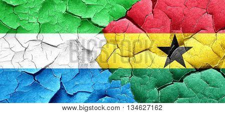 Sierra Leone flag with Ghana flag on a grunge cracked wall