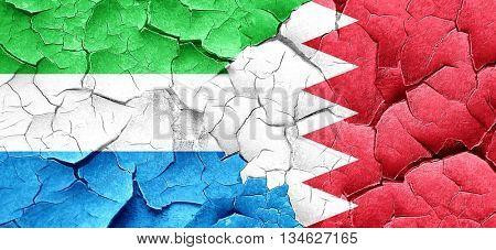 Sierra Leone flag with Bahrain flag on a grunge cracked wall