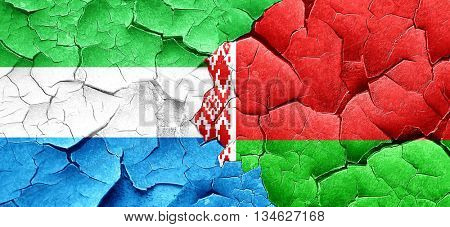 Sierra Leone flag with Belarus flag on a grunge cracked wall