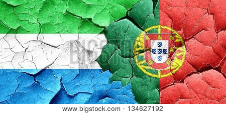 Sierra Leone flag with Portugal flag on a grunge cracked wall