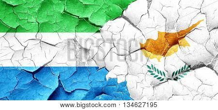 Sierra Leone flag with Cyprus flag on a grunge cracked wall