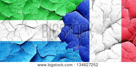 Sierra Leone flag with France flag on a grunge cracked wall