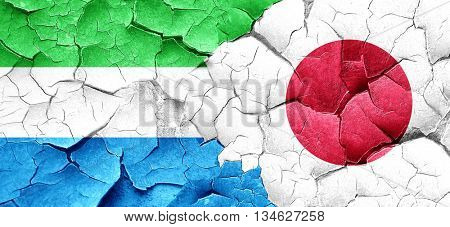 Sierra Leone flag with Japan flag on a grunge cracked wall
