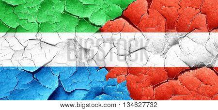 Sierra Leone flag with Austria flag on a grunge cracked wall