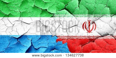 Sierra Leone flag with Iran flag on a grunge cracked wall