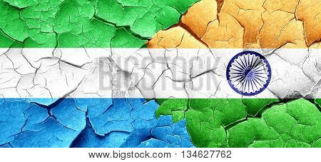 Sierra Leone flag with India flag on a grunge cracked wall