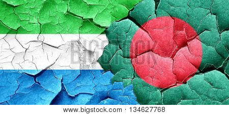 Sierra Leone flag with Bangladesh flag on a grunge cracked wall