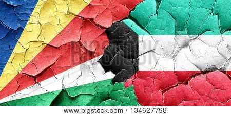 seychelles flag with Kuwait flag on a grunge cracked wall