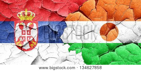 Serbia flag with Niger flag on a grunge cracked wall