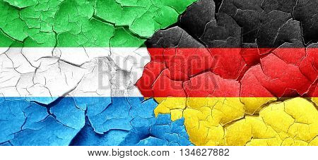Sierra Leone flag with Germany flag on a grunge cracked wall