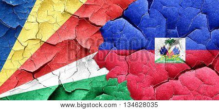 seychelles flag with Haiti flag on a grunge cracked wall