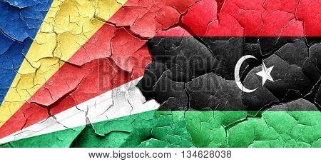 seychelles flag with Libya flag on a grunge cracked wall