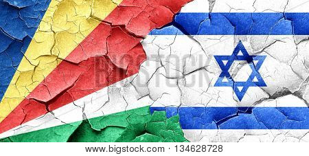 seychelles flag with Israel flag on a grunge cracked wall