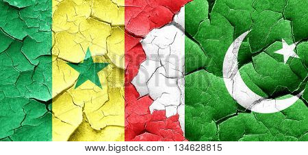 Senegal flag with Pakistan flag on a grunge cracked wall
