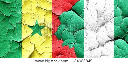 Senegal flag with Nigeria flag on a grunge cracked wall