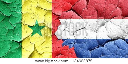 Senegal flag with Netherlands flag on a grunge cracked wall