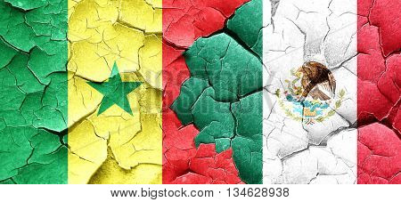 Senegal flag with Mexico flag on a grunge cracked wall