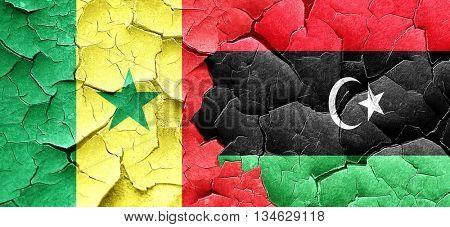 Senegal flag with Libya flag on a grunge cracked wall