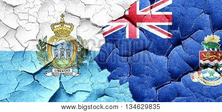 san marino flag with Cayman islands flag on a grunge cracked wal