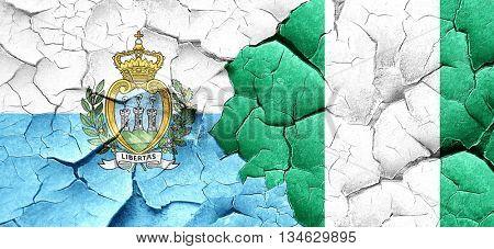 san marino flag with Nigeria flag on a grunge cracked wall