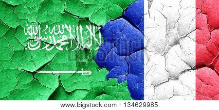 Saudi Arabia flag with France flag on a grunge cracked wall