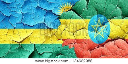 Rwanda flag with Ethiopia flag on a grunge cracked wall