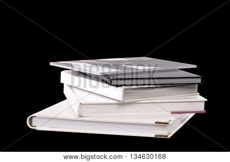 different sizes albums and books on a black background