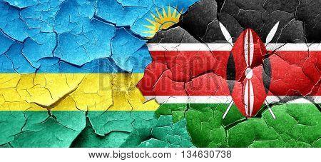 Rwanda flag with Kenya flag on a grunge cracked wall