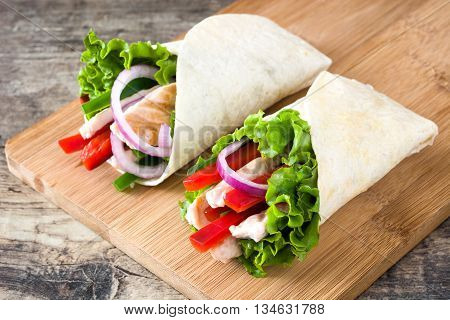 Mexican chicken fajitas with peppers lettuce and onion on a rustic wooden table