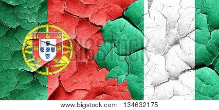 Portugal flag with Nigeria flag on a grunge cracked wall