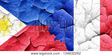 Philippines flag with France flag on a grunge cracked wall
