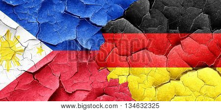 Philippines flag with Germany flag on a grunge cracked wall