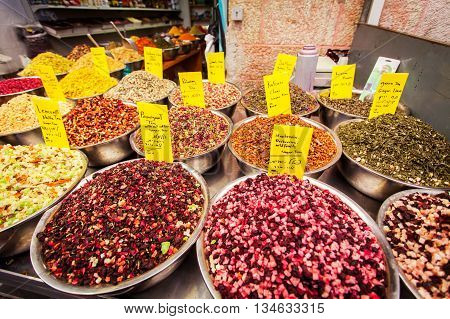 Different types of herbal tea with slices of dried fruit on the counter in Mahane Yehuda Market, Jerusalem, Israel. Cardamom tea, green tea, white tea, chocolate tea, Black tea, etc.