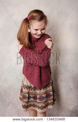 Little girl fooling in the studio hamming posing having fun